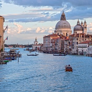 The Grand Canal view from the Accademy bridge, in the back ground the monumental church of plague : Santa Maria della Salute and the smaller Custom House with its tower surmonted by the golden sphere. To know more contact us on www.aguideinvenice.com