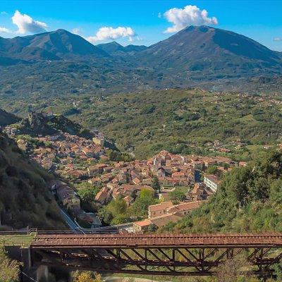 Sulla sinistra la Rocca dell'Armo, luogo storico e paesaggistico, dove è ubicato il Castello Ruggero. In primo piano il ponte in ferro della Ferrovia Calabro-Lucana, vincolato dal MiBACT