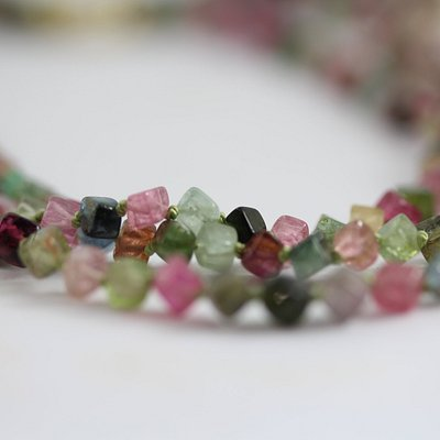 Multicoloured tourmalines in this 3 strand necklace with handmade gold catch.