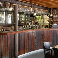 La première vue en entrant, un bar à la déco brute, de style industriel.