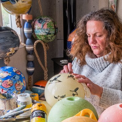 Donna painting the floats and buoys that have been collected from the beaches on the Isle of Skye.