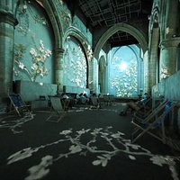 Projections cover the walls and the floor, dancing over visitors seated in socially-distanced deck chairs.