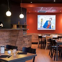 Salle de restaurant, pizzas cuites dans notre four à bois devant le client !