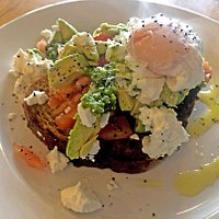 The delicious Avocado, Feta & Tomato Toast , topped with an extra egg. Beautiful and filling meal with basil pesto.