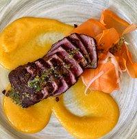 Jamaican jerk seared Ahi tuna, pickled carrot & leek ribbons, mango oculus and salsa verde.