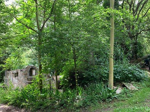 """Idyllisch zwischen Bäumen und Planzen am Wasser, liegt die """"Simonsburg"""". Eine von Werner Scheidweiler gebaute Burgruine."""
