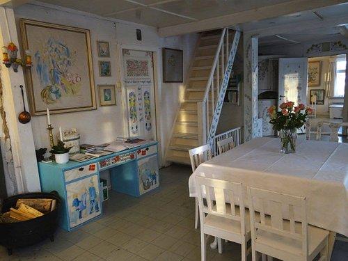 Stua med spisebord, pulten er dekorert av Ingrid Book, døren til kjøkkenet av Birgit Abrahamsen, bak ser vi inn i den innerste stua.