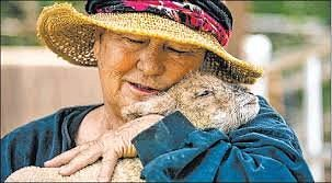 Founder, Sharon Linsenbardt cuddling a beloved lamb