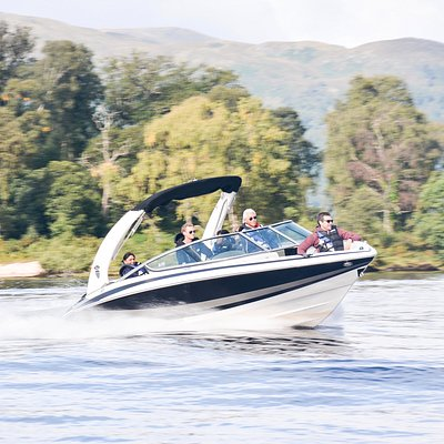 A family enjoying a luxury speedboat tour of Loch Lomond with an island in the background.