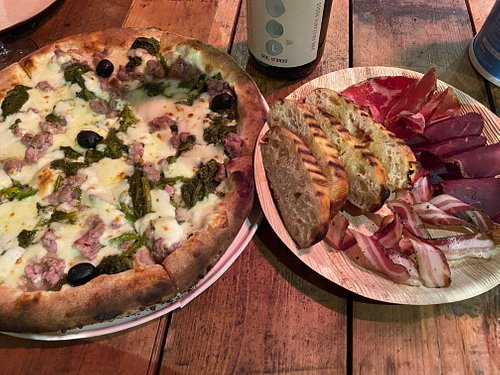 Pizza salsiccia with brocoletti (white pizza without tomato sauce) and a plate of charcuterie with home-baked bread and olive oil drizzle