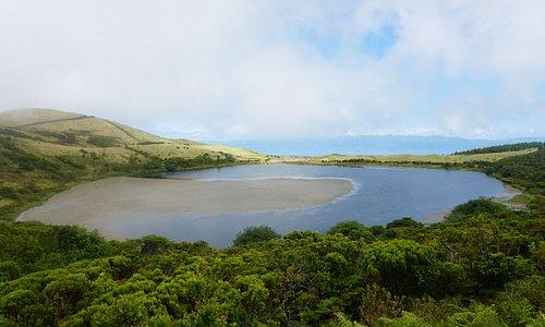 Lagoa do Caiado, com o mar e a Ilha de São Jorge no horizonte.