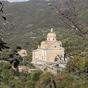 The church, scenically located in a frame of wooded hills, seen from the viewpoint of Piazza Mazzini.
