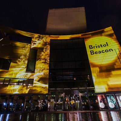 The iconic front of Bristol Beacon taken in September 2020 lit with projections created by Limbic Cinema of artists who have performed at the venue. Photo by Dominika Sheibinger.