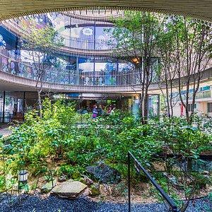 통의동 블릭웰(BrickWell) 1층으로 시민들이 지나고 있다. 1층에 마련된 작은 연못과 정원은 우측의 백송 터로 연결된다.