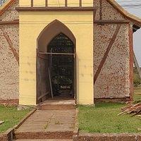 Igreja pequena se destaca na paisagem rural. Em obras de restauro.