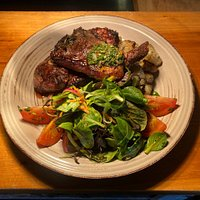 Patagonia BBQ slow cooked Lamb served with roast potatoes, tomato and lettuce salad and chimichurri sauce.