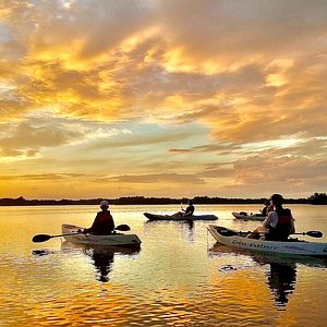 Kayakers relax and watch the sunset over the Thousand Islands Conservation Area on a Kayak Eco Tour with Fin Expeditions. Come experience the other side of Cocoa Beach!