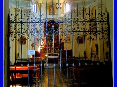 """Il Luminoso interno con cancellata d'ingresso e, sullo sfondo, la grande pala del """"Duchino""""."""