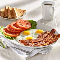 Five strips of thick bacon, three eggs, and freshly sliced tomatoes served with thick toast.