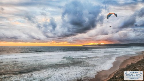 Sunset Flight from Wilderness with a Tandem Paraglider , Dolphin Paragliding has 25 years and our pilots have thousands of hours flight experience , to make the experience wonderful .