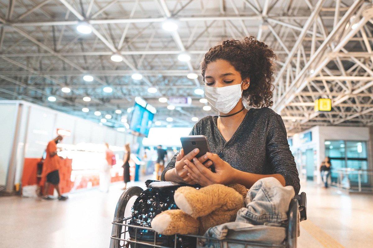 Ung maskeret kvinde i lufthavnen