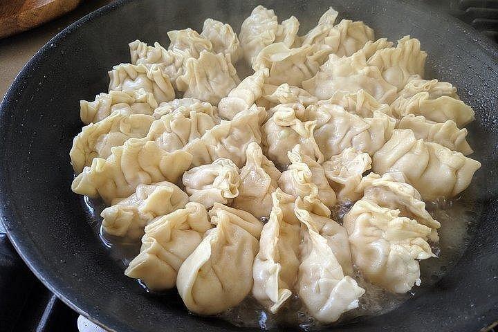 Steaming dumplings in a wok.