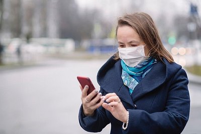 Masked woman in a blue coat consulting her phone outside.