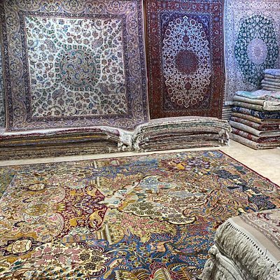 One of Sheba Iranian Carpets and Antiques Stores showrooms. Magnificent Persian carpets of silk and wool and silk adorn the walls. A beautiful Tabriz hand knotted pictorial rug is on the floor and there are gorgeous rugs stacked in bundles.