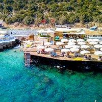 Çakıl Beach Club Kalkan'da turkuaz mavisi koyu, konforlu şezlong ve minderleriyle Akdeniz'in mavi bayraklı sularının keyfini sürebileceğiniz bir tesis.