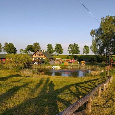 Widok na kąpielisko i staw po którym możecie pływać rowerami wodnymi, widoczna w oddali Karczma Bartbo serwuje ciepłe posiłki i smaczne posłki.