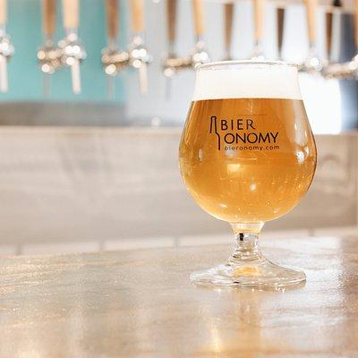 Intérieur rapproché du bar Bieronomy (situé à l'arrière de la cave) avec le logo et le verre du bar.