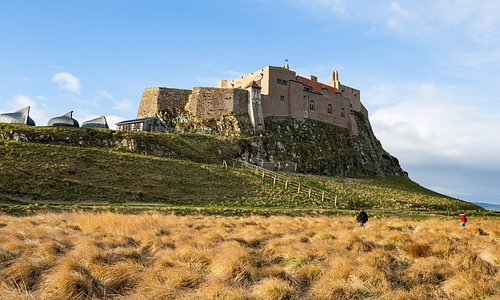 Lindisfarne castle viewed across the field, basking in sunshine