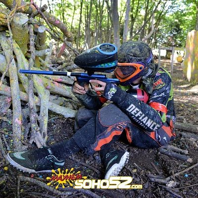 Paintball player crouching behind a barricade