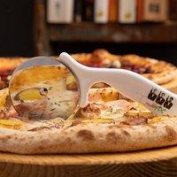 """questa foto descrive """"semplicemente noi"""": tagliere di legno, rotella e pizza a hoc"""