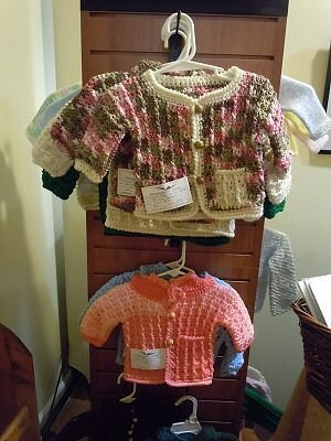 The gallery has baby sweaters knitted and crocheted by local artisans.