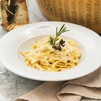 AL PARMIGIANO REGGIANO Fettuccine (pasta larga) preparada en la rueda de Parmigiano Reggiano.
