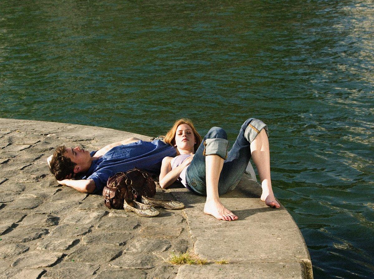 Man en vrouw liggen in de zon naast de rivier de Seine in Parijs, Frankrijk