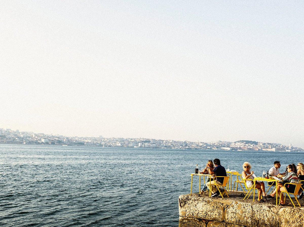 Een groep mensen zit in gele stoelen aan zee in Lissabon.