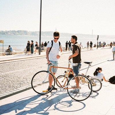 Twee mannen met fietsen langs het water in Lissabon