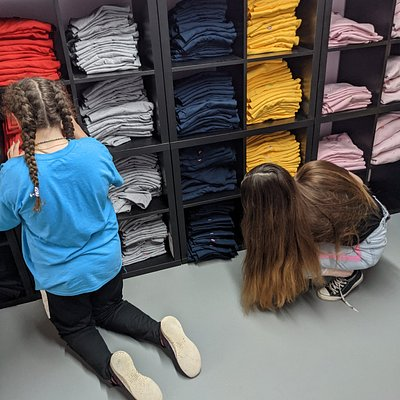 The girls pick the t shirts they are goin to design from the wall of shirts.