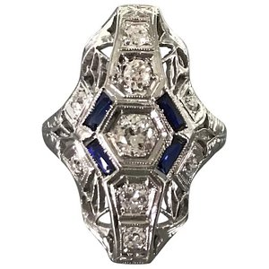18K Art Deco Diamond and Sapphire Dinner Ring with GIA Appraisal Report. This period sparkler shows 9 old European-cut diamonds weighing .50 carats and 4 bezel-set synthetic blue sapphires weighing .28 carats.   Appraised Value: $2,997.30  Our Price: $2,395 Item Number: ACC-3724