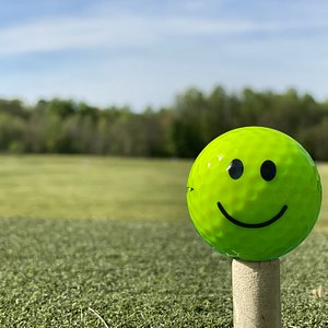 Smiley golf ball on tee.