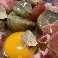 Alcachofas naturales en salsa de trufa, con jamón ibérico y yema de huevo. (Temporada)