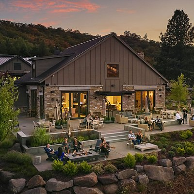 Sun sets over our tasting room patio while a few guests linger to enjoy the sunset and the warmth of the fireplace.