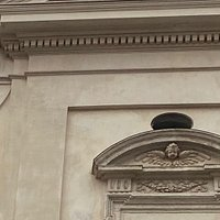 Above is an entablature with a dentillated frieze (odd), and then a crowning projecting triangular pediment containing the coat of arms of Pope Paul V.