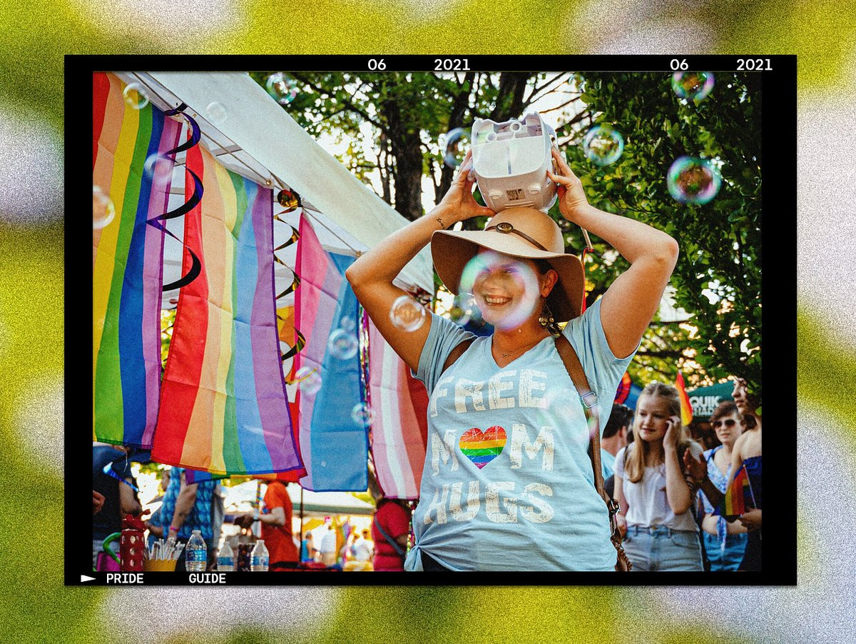 Photo of woman holding a bubble machine on her head, standing near pride flags