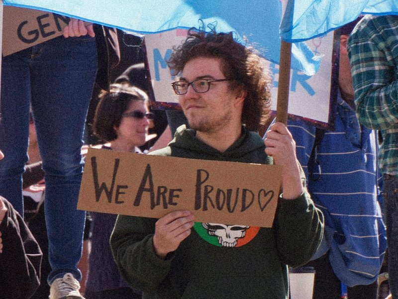 Person standing with 'We Are Proud' sign and holding a Transgender Pride flag