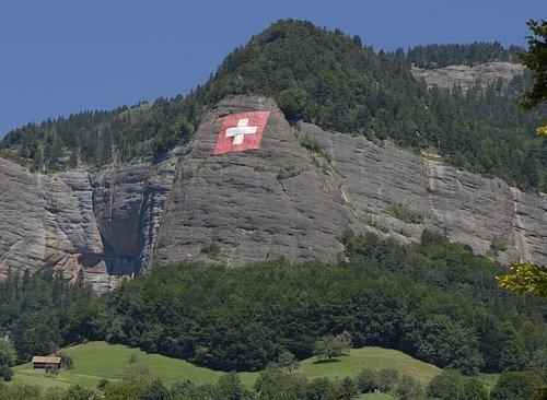 Drapeau suisse sur le rocher dominant Vitznau (LU) en Suisse centrale aux abords du lac des Quatre-Cantons.