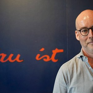 """Thomas Vogler in seiner Bar vor dem großen Bild """"Blau ist eine Farbe vor gelb"""" von Cosy del Piero"""