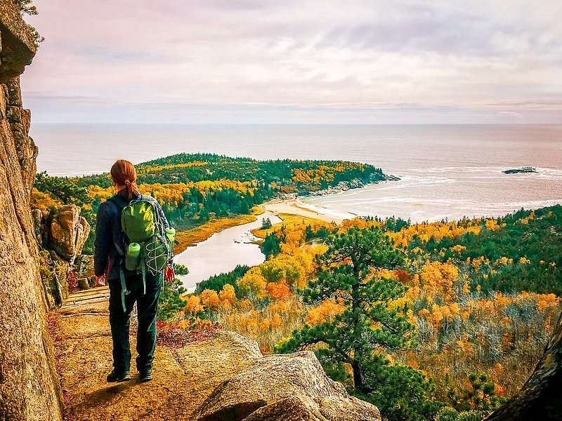A hiker takes in gold and red leaves next to a high cliff from an overlook at Beehive Mountain